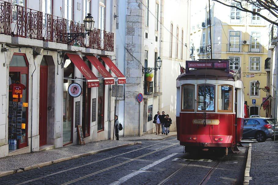 Ascenso de un tranvia rojo por una de las calles del barrio de Alfama, en Lisboa.