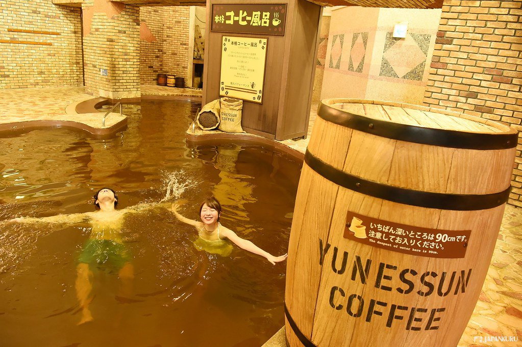 Dos personas bañándose en un onsen de café en Kowakien Yunessun