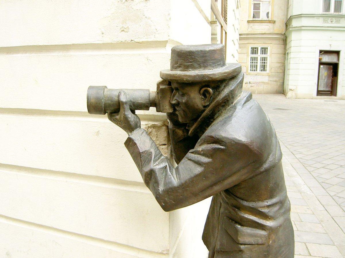 La escultura del papparazzi sacando fotos desde una esquina.