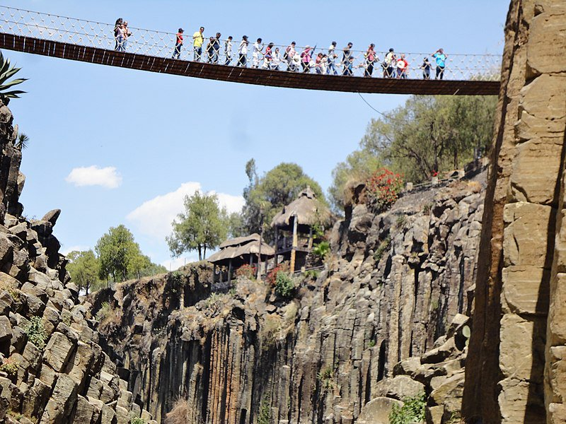 Personas atravesando el puente colgante de los Prismas Basálticos.